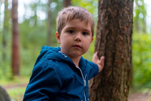 Garçon dans une veste bleue se tient près d'un arbre dans un parc et se penche sur la caméra