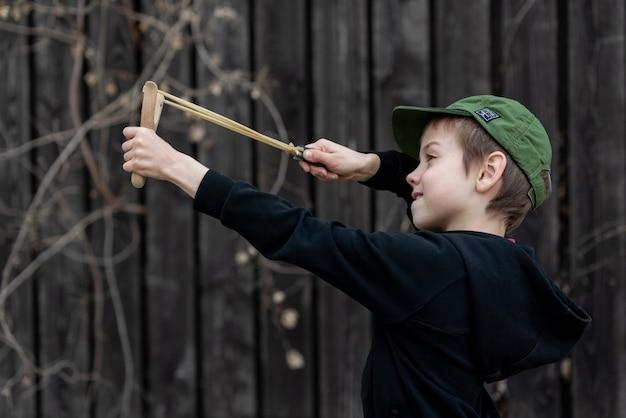 Un garçon dans une veste noire avec une capuche et une casquette tire d'un arrière-plan flou de fronde