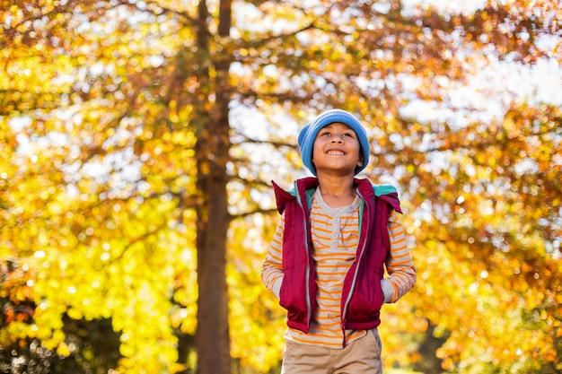 Garçon debout contre les arbres d'automne au parc