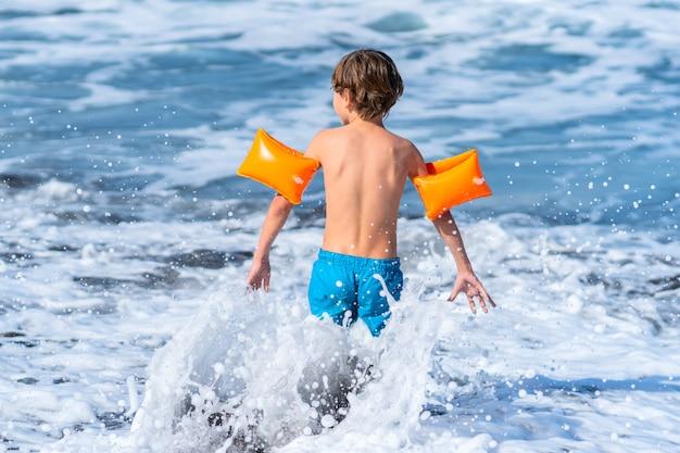 Le garçon debout vers les vagues de la mer. l'enfant porte des manches de bras.