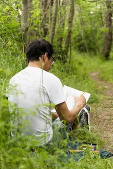 Garçon dessin au fusain dans le bois