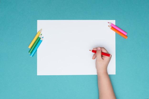 Le garçon dessine sur une feuille de papier blanc