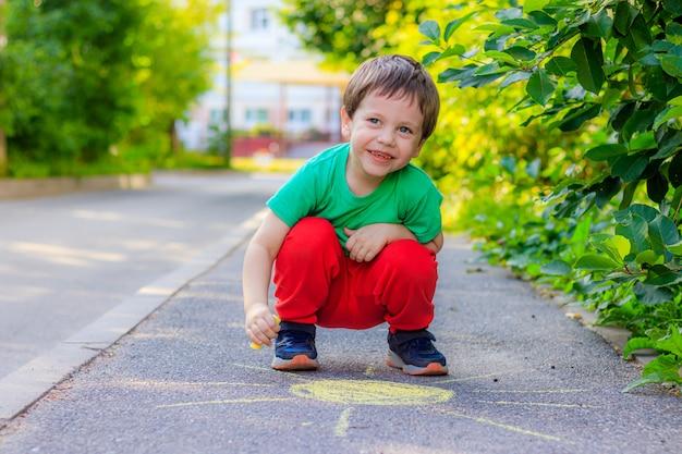 Un garçon dessine le soleil sur l'asphalte avec des crayons