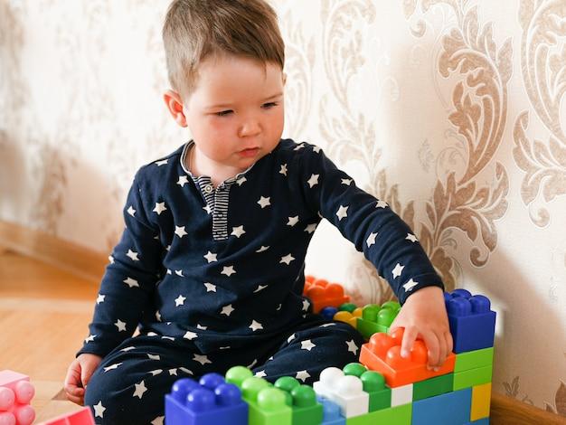 Garçon de deux ans jouant avec le constructeur de couleur