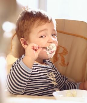 Un garçon de deux ans mange de la bouillie le matin.