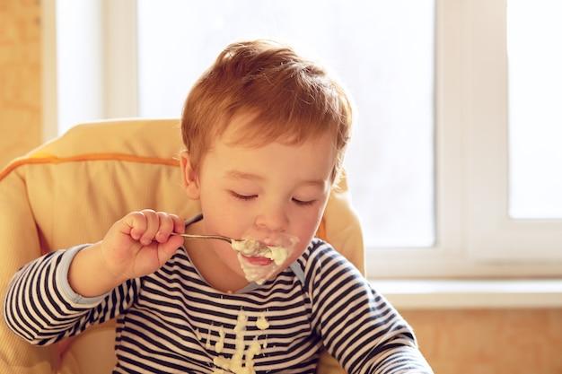 Garçon de deux ans mange du porridge le matin.