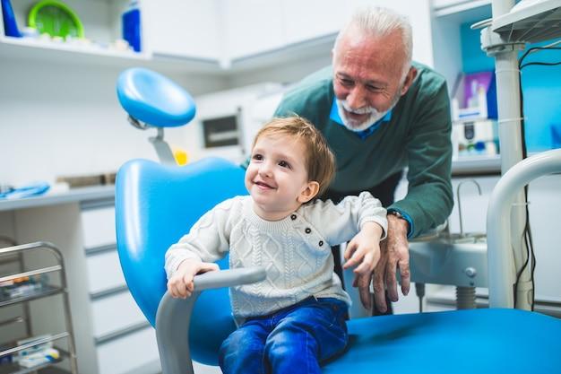 Garçon de deux ans avec son grand-père pour la première fois sur un fauteuil dentaire.