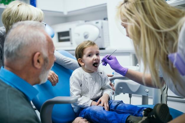 Garçon de deux ans avec son grand-père et sa grand-mère pour la première fois en cabinet dentaire