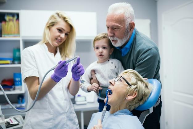 Garçon de deux ans avec son grand-père et sa grand-mère pour la première fois en cabinet dentaire.