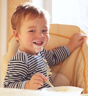 Un garçon de deux ans sourit et mange du porridge.
