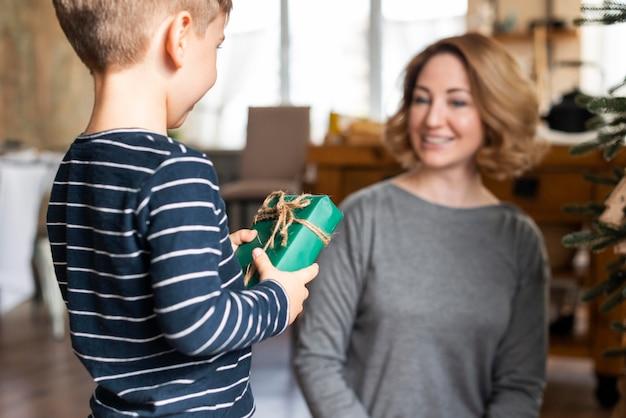 Garçon donnant un cadeau de noël à la mère