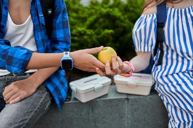 Un garçon donne une pomme pendant le déjeuner près de l'école en gros plan.