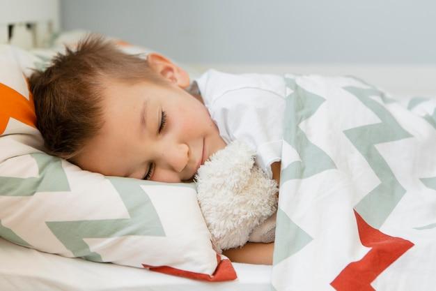 Garçon dormant avec son jouet préféré