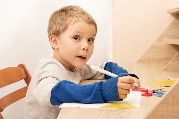 Un garçon drôle au visage surpris s'assoit à la table, tout en dessinant ou en écrivant. concept d'éducation à domicile ou activités de développement. apprentissage en ligne.