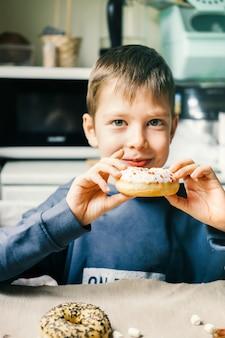 Garçon drôle avec beignet. l'enfant s'amuse avec le beignet. nourriture savoureuse pour les enfants. bon moment à la maison avec des aliments sucrés.
