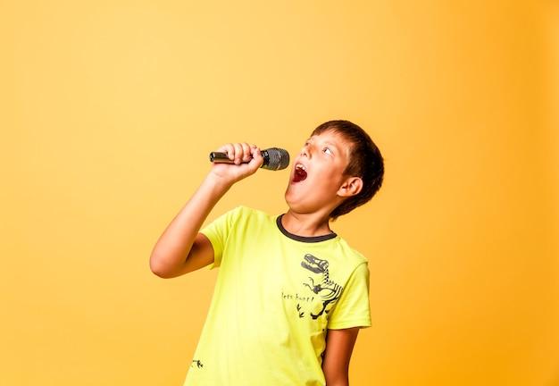 Garçon drôle chantant avec le microphone sur le fond jaune
