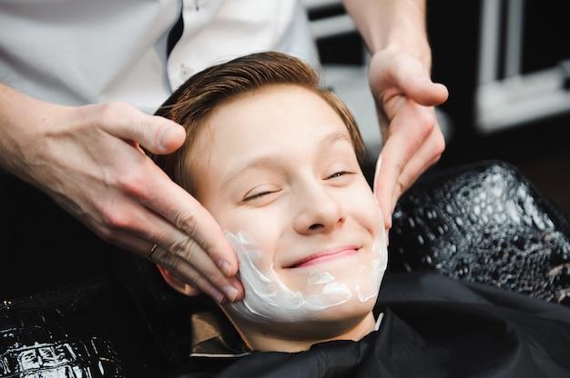 Garçon drôle dans une cape de salon noir dans le salon de coiffure