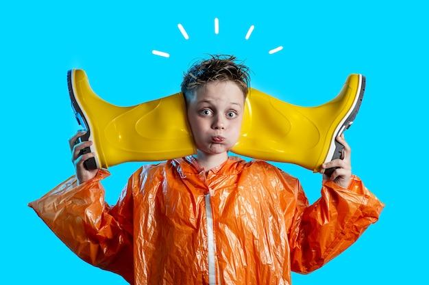 Garçon drôle dans un manteau orange avec des joues gonflées et des bottes en caoutchouc sur fond bleu