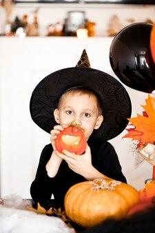 Garçon drôle d'enfant dans le costume de sorcière pour halloween avec jack citrouille dans les mains