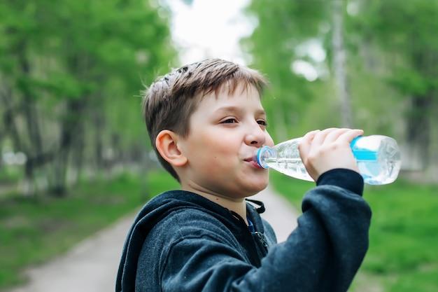 Garçon, eau potable, depuis, a, bouteille plastique