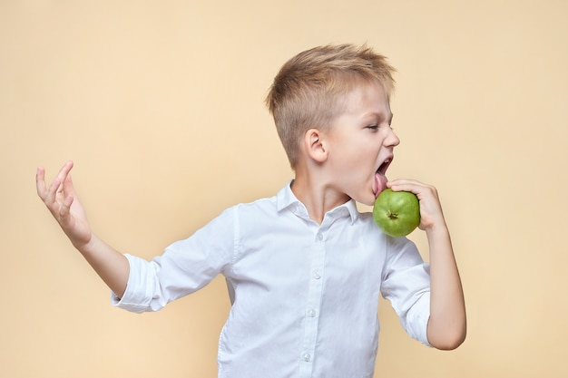 Un garçon échevelé mignon se laisse aller et lèche une poire dans ses mains.
