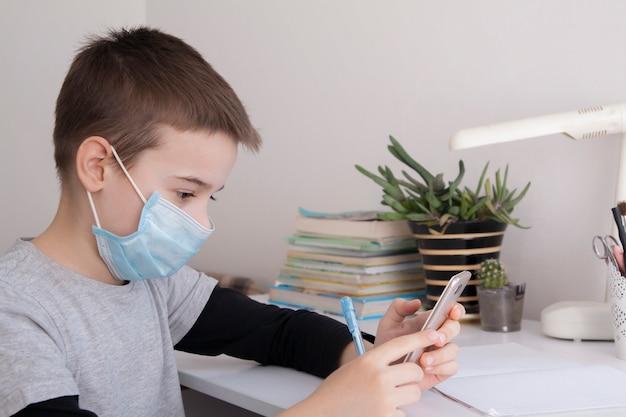 Garçon à l'école à domicile avec un smartphone dans ses mains et un masque médical. concept de quarantaine de coronavirus