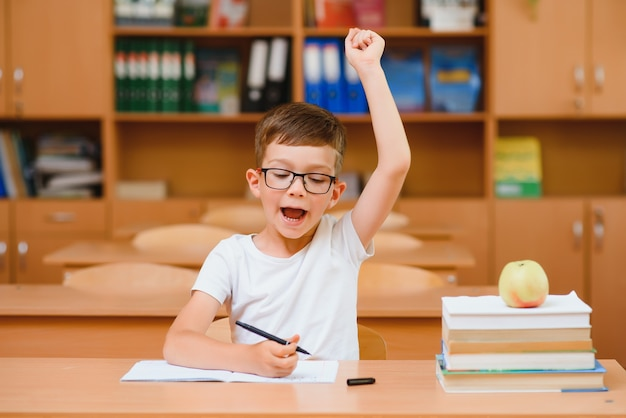 Garçon de l'école primaire au bureau de la classe essayant de trouver de nouvelles idées pour le travail scolaire.