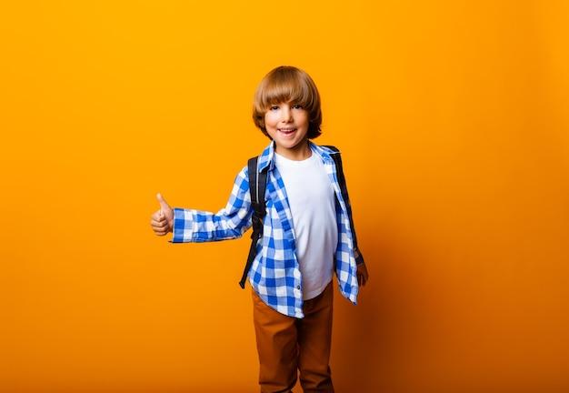 Garçon d'écolier enfant montrant les pouces vers le haut isolé sur fond jaune