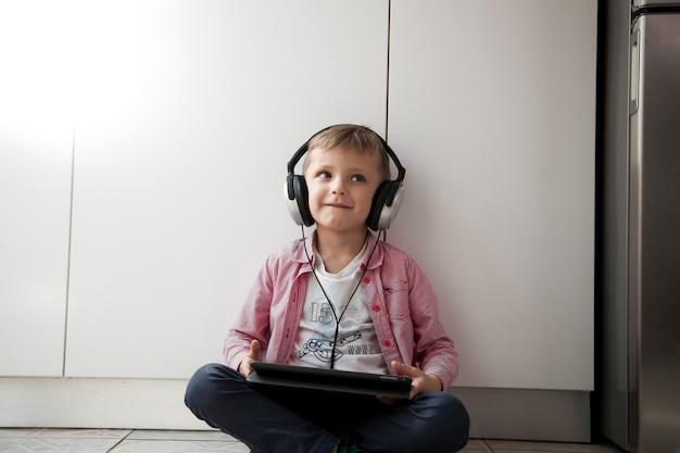 Garçon écoutant de la musique sur le sol