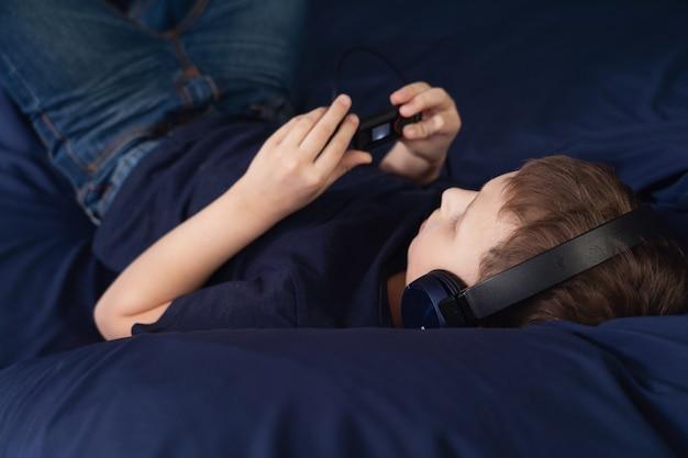 Garçon, écouter musique, dans, écouteurs, coucher lit