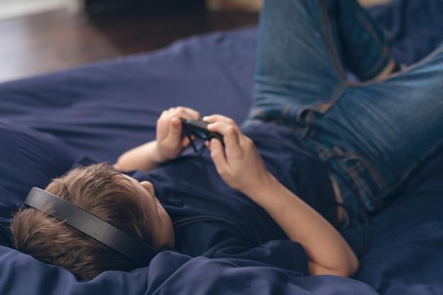 Garçon, écouter de la musique dans les écouteurs en position couchée dans son lit, mise au point sélective sur la tête