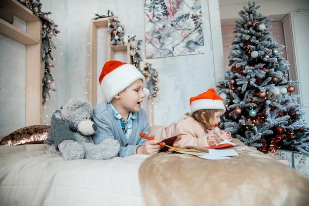 Le garçon écrit au père noël. soirée familiale de noël. cadeaux de nouvel an. salon lumineux décoré
