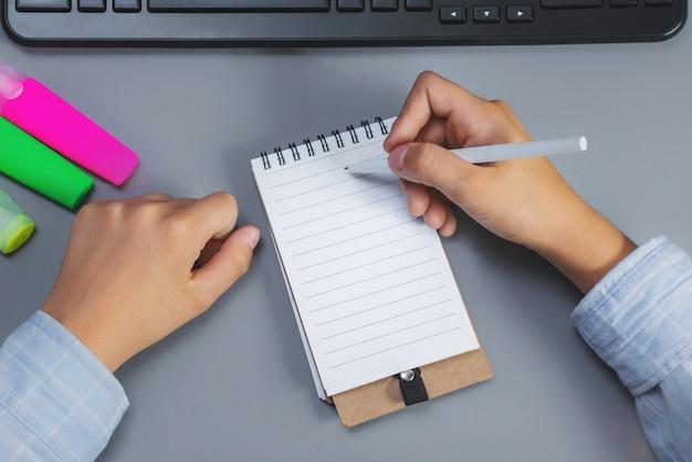 Garçon écrit dans un ordinateur portable sur un bureau.