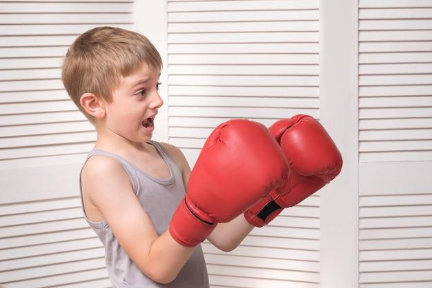 Garçon effrayé dans des gants de boxe rouges.