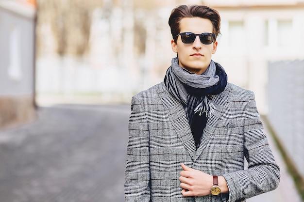 Garçon élégant en lunettes de soleil en manteau avec une mallette sur la rue