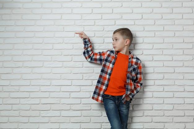 Garçon élégant à la mode près du mur de briques blanches