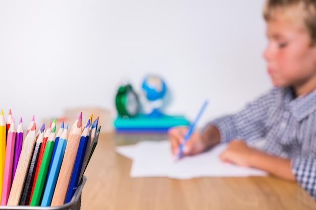 Garçon, élève travaillant, apprenant, étudiant à la maison, prenant des notes dans le bloc-notes. étudiant, éducation, rester à la maison, concept d'enseignement à domicile