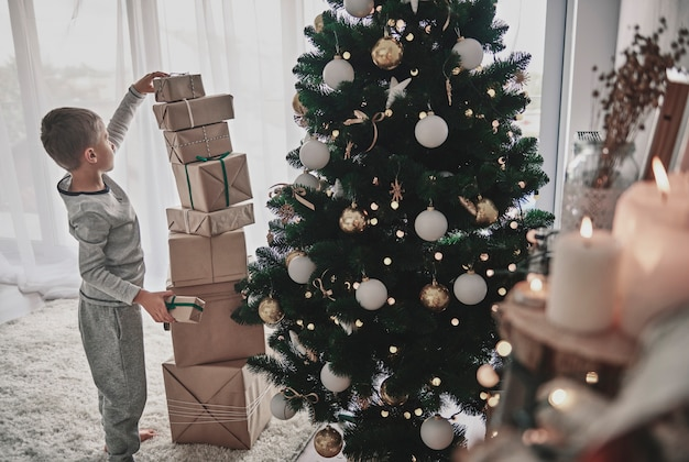 Garçon empiler des cadeaux de noël à côté d'un arbre de noël