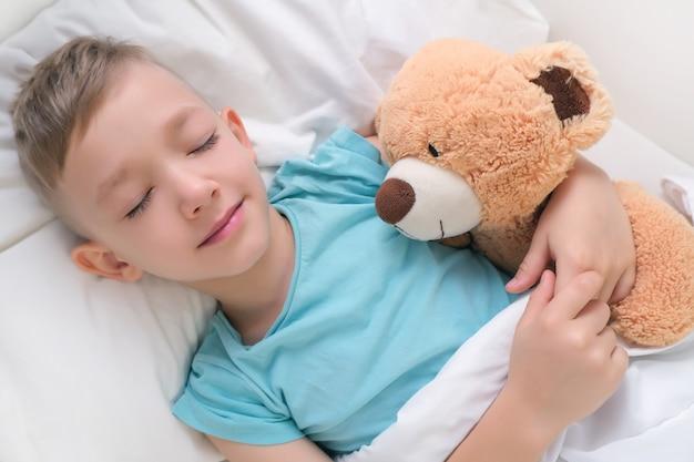 Garçon endormi doucement étreignant un ours en peluche