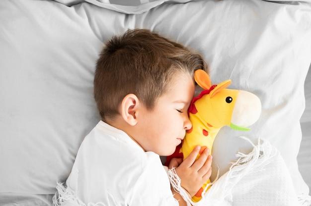 Le garçon endormi était allongé sur le lit avec une girafe dans les mains. photo de haute qualité