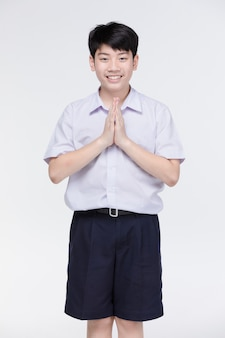 Garçon enfant asiatique en uniforme d'étudiant, acteur sawaddee signifie bonjour.