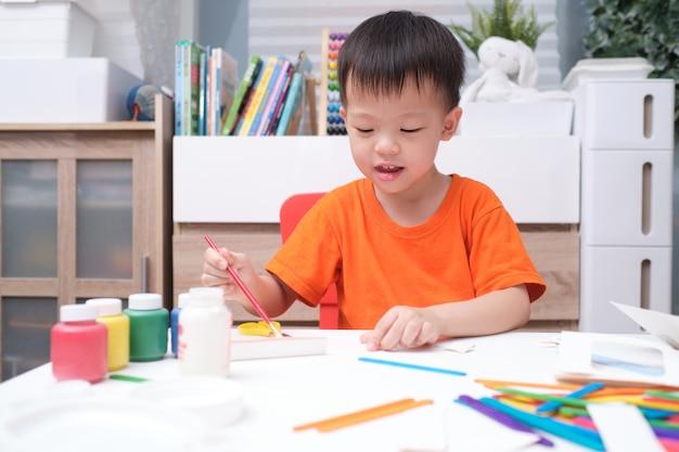Garçon enfant en bas âge asiatique aiment utiliser de la colle faisant des arts à la maison