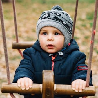 Garçon enfant en bas âge avec des vêtements chauds sur la bascule