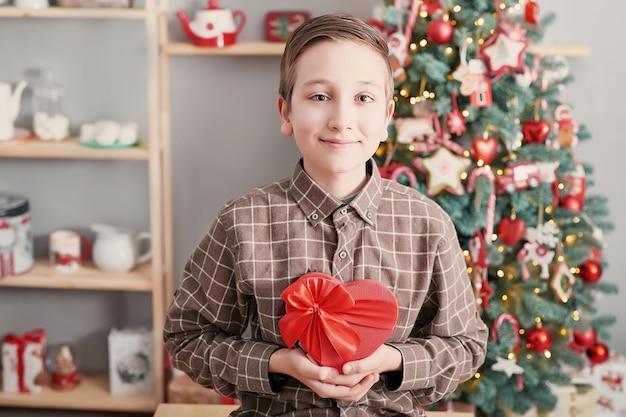Garçon enfant avec boîte-cadeau et arbre de noël.