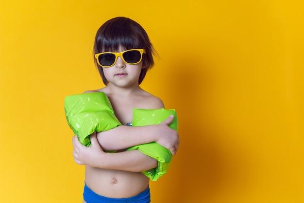 Garçon enfant en brassards de bain vert gonflable et lunettes de soleil se dresse sur un mur jaune