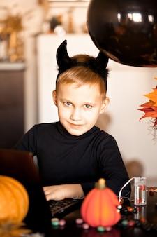 Garçon enfant drôle en costume maléfique pour halloween à l'aide d'un ordinateur portable tablette numérique. appelez en ligne des amis ou des parents.