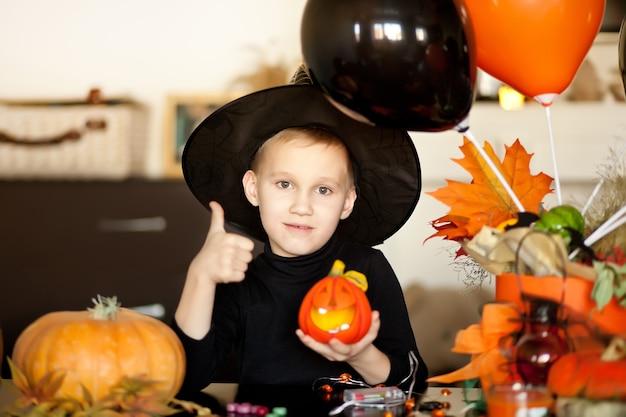 Garçon enfant drôle en costume de sorcière pour halloween avec jack citrouille dans une main.
