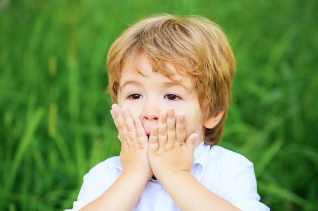 Garçon enfant drôle avec les mains près du visage isolé sur fond vert