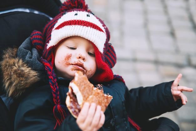Garçon enfant mangeant du trdlo frais chaud appétissant ou trdelnik avec du chocolat à cesky krumlov