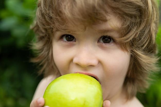 Garçon enfant mangeant une pomme dans un parc dans la nature